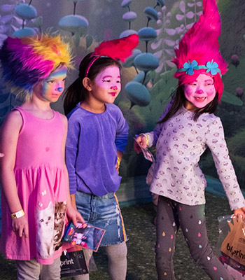 Three young girlfriends in Trolls face paint and wigs pose for a selfie together