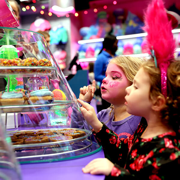 Two adorable little girls looking into a glass display of sweet treats