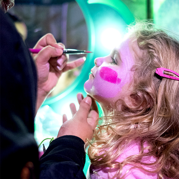 Young girl getting Trolls face painted by a Glitter Guru at the Salon Experience