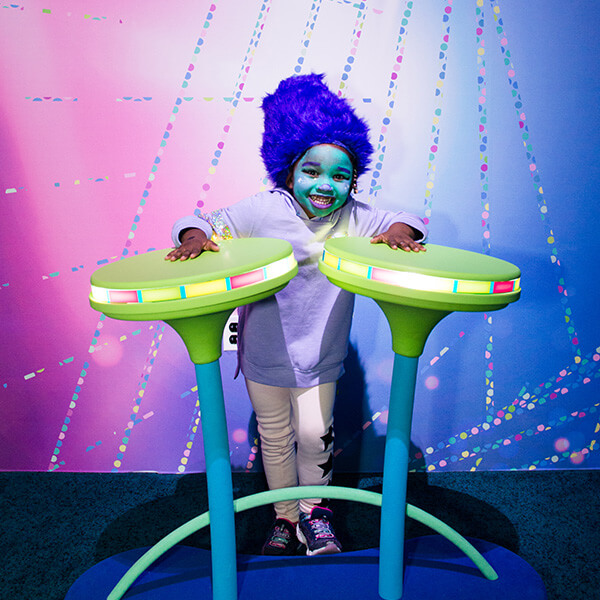 Fun little girl in Trolls face paint and wig playing electronic drums