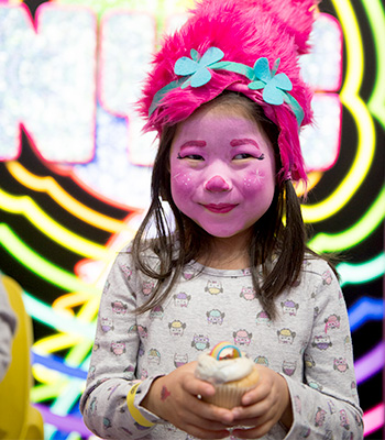 Adorable little girls in full Trolls face paint and wig holding a delicious cupcake.