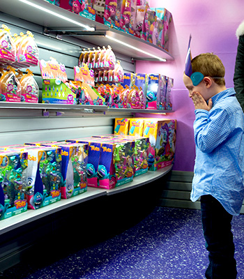 Young boy staring at all the Trolls merchandise inside the gift shop.