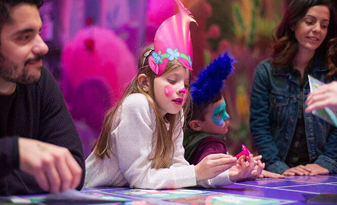 Kids with face paint & Trolls wigs scrapbooking together at the After Party area