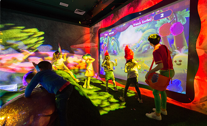 Kids encouraged to play together with a wall-sized digital game at the Critter Creek