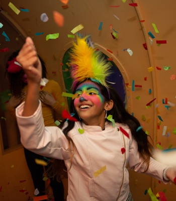 Young girl with Trolls makeup grabs confetti inside the Sparkle On Caterbus