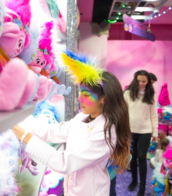 Young girl checking out Trolls plush at the souvenir gift shop