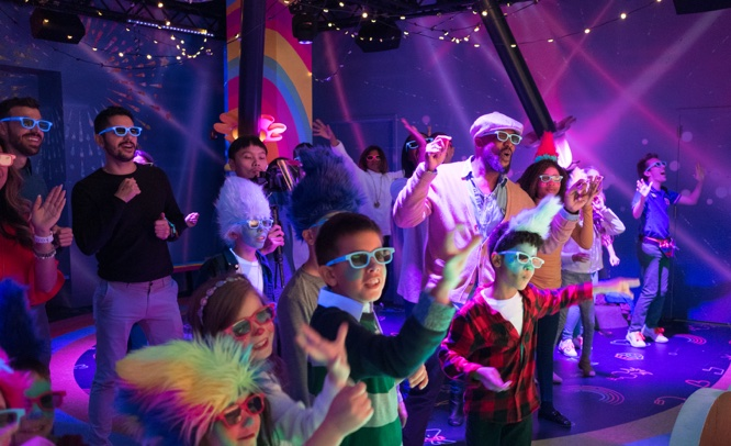 large group of kids and parents with 3D glasses watching and dancing inside Poppy's Best Day Ever Celebration