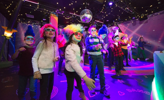 Boys and girls with 3D glasses watching and dancing inside Poppy's Best Day Ever Celebration