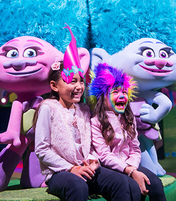 Two girls with Trolls wigs laughing while posing for a selfie with Satin & Chenille