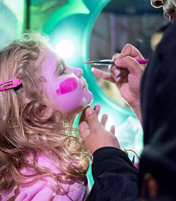 Cute little girl getting Trolls face paint by a Glitter Guru